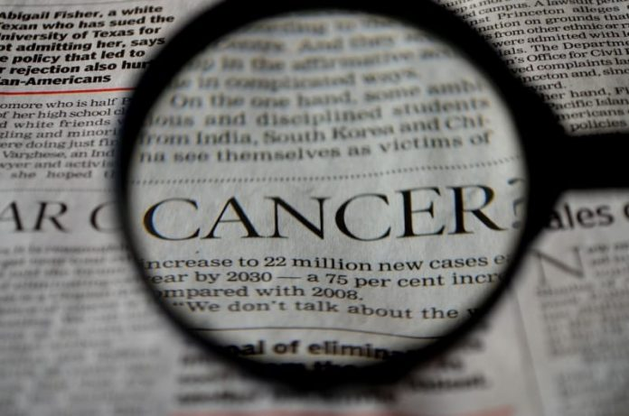 image d'une page de journal avec le mot cancer passé à la loupe